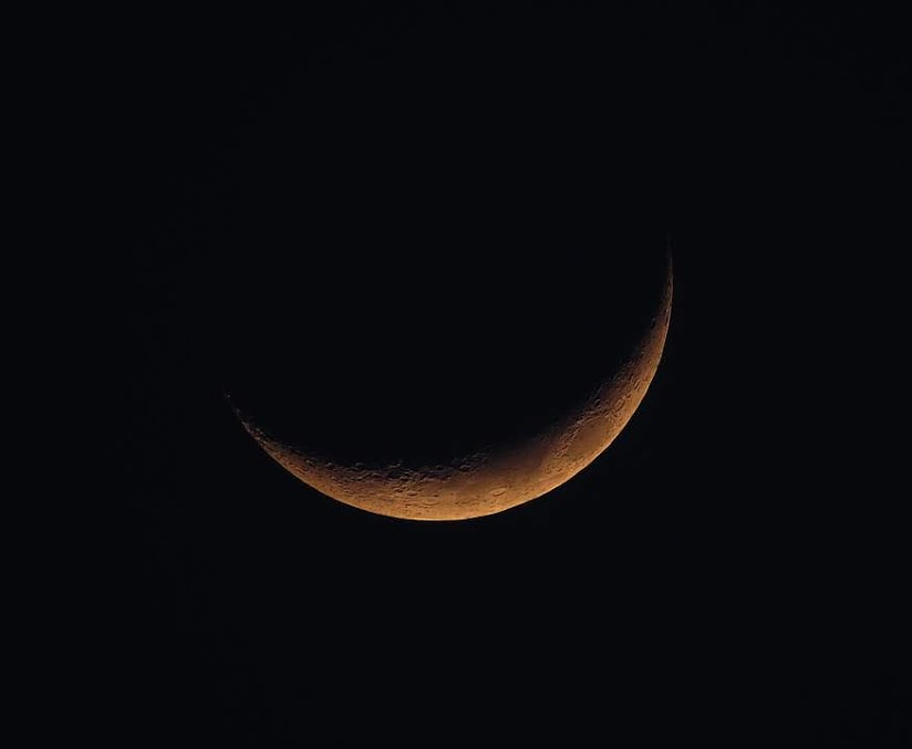 This image shows a black sky with a sliver of moon visible.