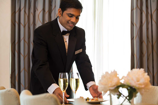 seven-seas-voyager-master-suite-butler.jpg - A butler prepares Champagne and canapes in the Master Suite of Seven Seas Voyager.