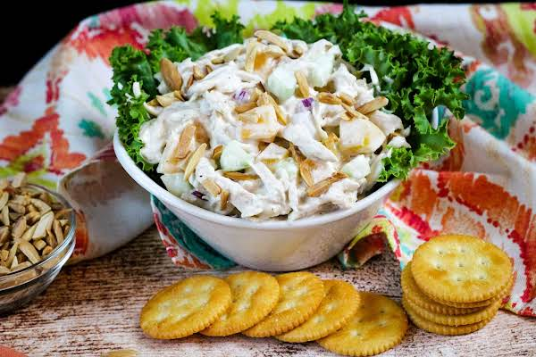 A Bowl Of Chicken Salad With Fresh Peaches With Crackers.