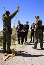 Photo: A U.S. Border Patrol agent in Nogales, Ariz., March 31 shows a group of U.S. bishops an improvised ladder immigrants use to make their way unlawfully over the U.S.-Mexico border fence. Nine bishops took part in a two-day tour focused on border issues in Nogales. They used the opportunity to again appeal for changes in the U.S. immigration system. The bishops pictured from left are Auxiliary Bishop Eusebio L. Elizondo of Seattle, Bishop John C. Wester of Salt Lake City and Bishop Gerald F. Kicanas of Tucson, Ariz. The bishops were celebrating a Mass April 1 in memory of those who have died trying to cross the border. (CNS photo/Nancy Wiechec) (April 1, 2014)