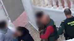 Agentes con los menores saliendo de la vivienda.