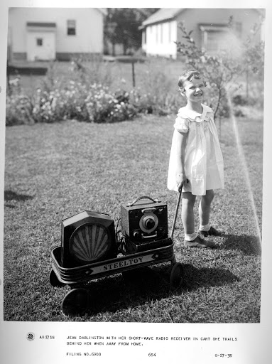 Jean Darlington with her short-wave radio receiver in cart she trails behind here when away from home.