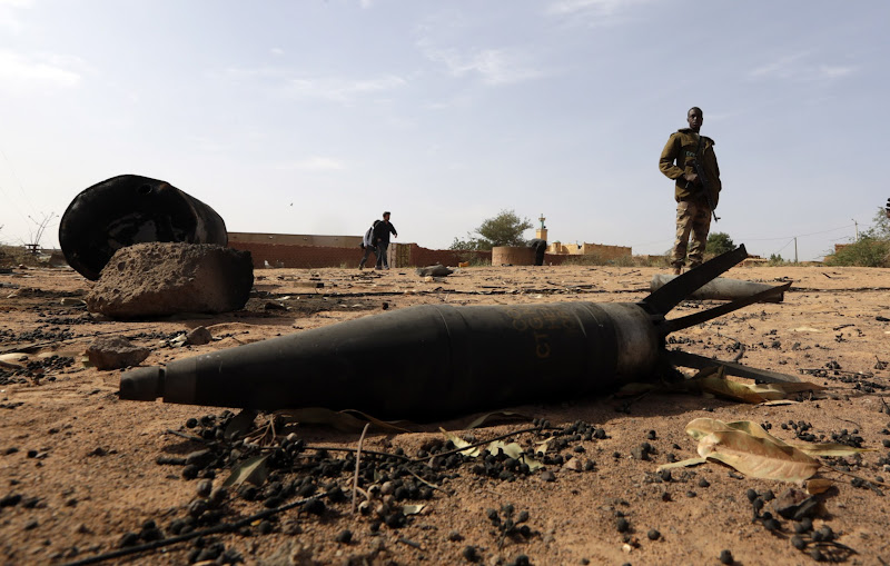 Photo: A Malian soldier is seen near an unexploded shell in the recently liberated town of Konna January 26, 2013.     REUTERS/Eric Gaillard (MALI - Tags: CIVIL UNREST CONFLICT MILITARY TPX IMAGES OF THE DAY)