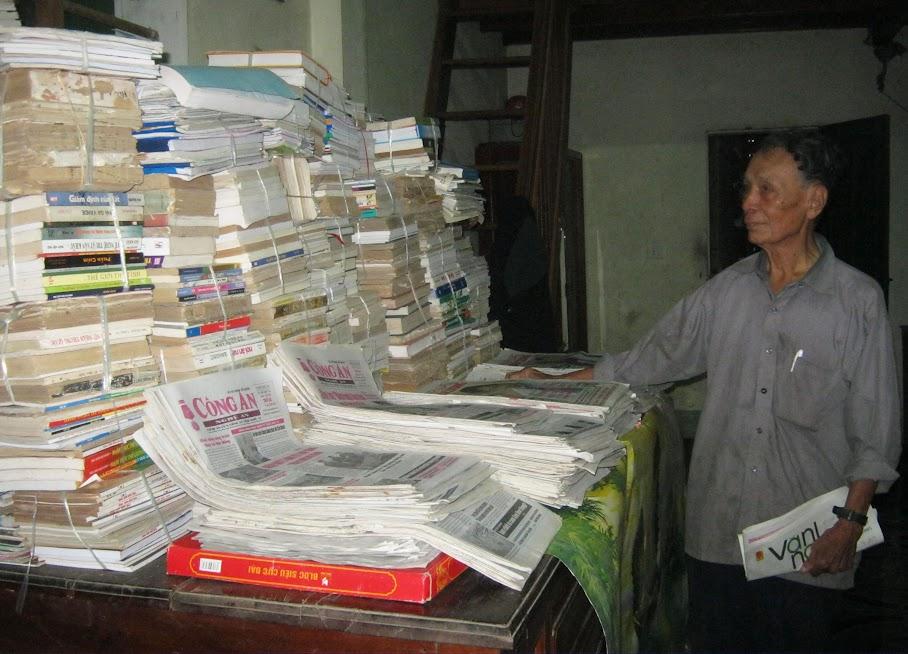Thầy giáo Lâm Văn Khoa bên những chồng sách, báo cũ mà mình sưu tầm được
