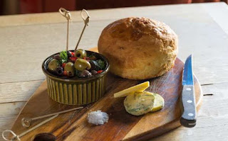 bread, cheese and bowl of olives on bread board