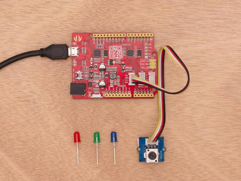 Components of a mini starter STEM kit are laid out on a table. The Arduino board is plugged into a USB cable.