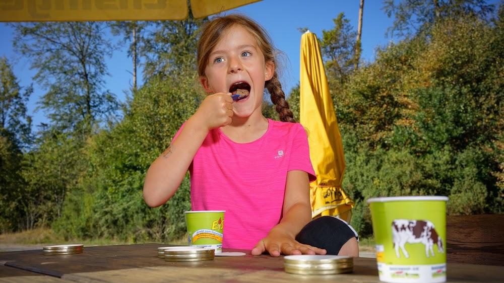 Ein Mädchen genießt an einem warmen Sommertag das leckere Bauernhofeis