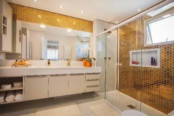 Banheiro com pastilhas em formato hexagonal dourado, armários brancos, box de vidro e detalhes dourado.