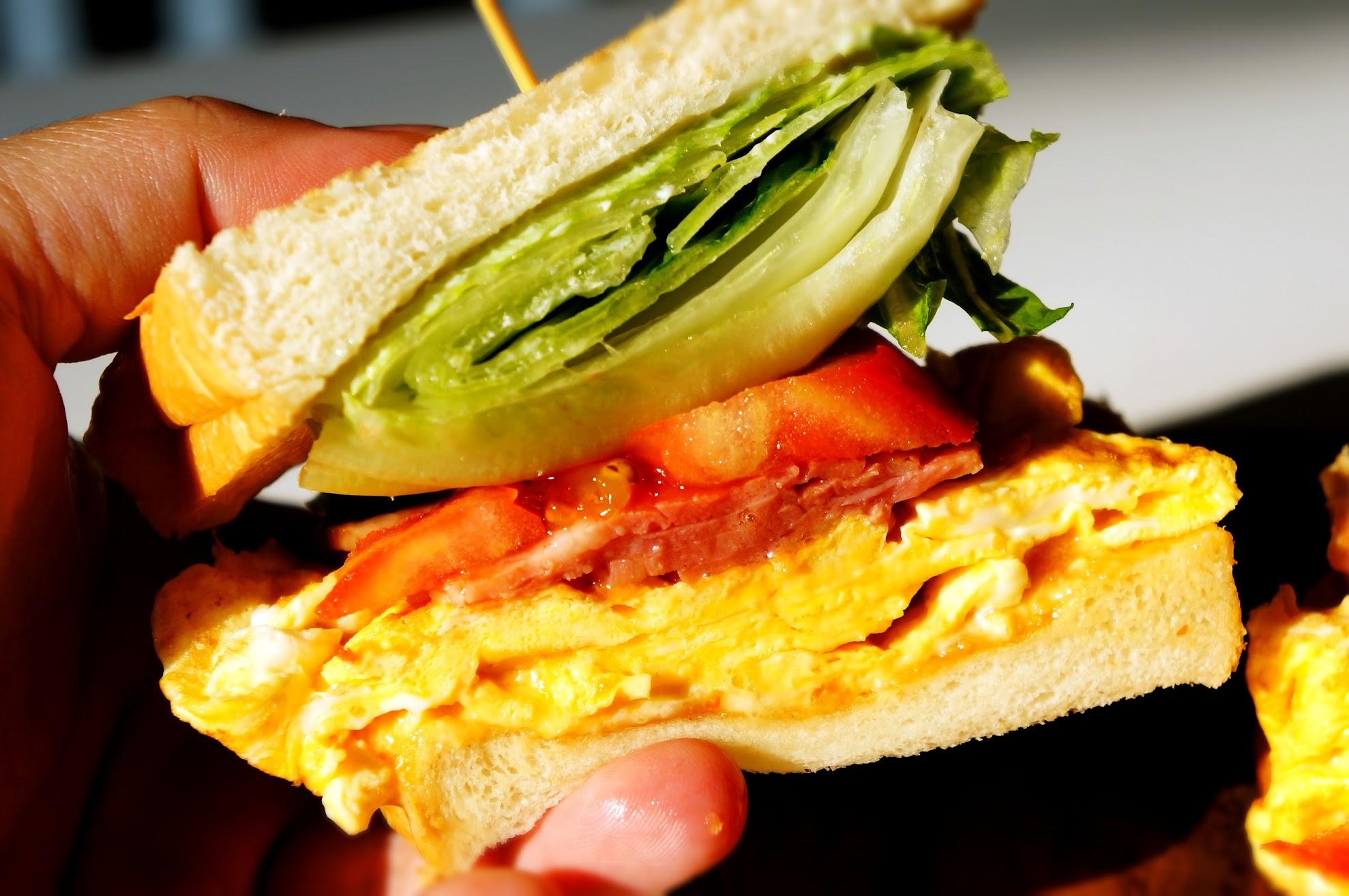 一般烤脆的吐司,中間夾著生菜、番茄、培根和蛋,麵包上有塗上花生醬