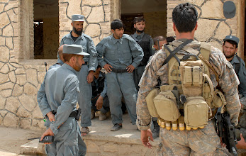 Photo: A Special Operations Task Force – South senior weapons sergeant conducts an after-action review with policemen from 3rd Battalion, 3rd Afghan National Civil Order Police Brigade, following a joint patrol Aug. 28 through the Arghandab River Valley, Kandahar Province, Afghanistan.  A 20-man team from SOTF-S is partnered with 3rd Battalion and conducts joint patrols and training with the unit in order to increase their proficiency.  (U.S. Army photo by Staff Sgt. Jeremy D. Crisp / Special Operations Task Force – South).