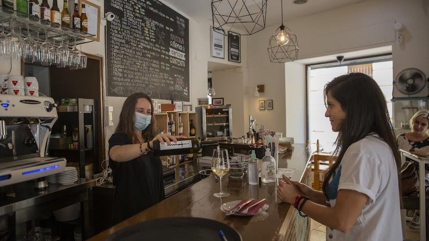 Una camarera sirve una copa de vino a una clienta.