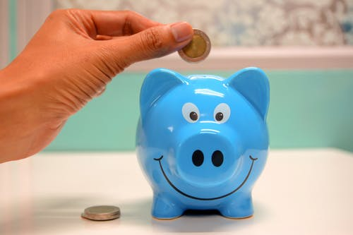 Person putting coins in a piggy bank.