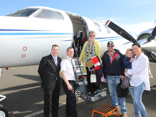 FIRST PASSENGERS: All aboard for Brisbane as Fly Corporate's sales manager Geoff Woodham and Captain Damon Banks welcome passengers aboard the first service to Brisbane on Monday, from left, Helen Hanns, Mark Ratcliffe and Brighid Campbell with Joe Campbell.