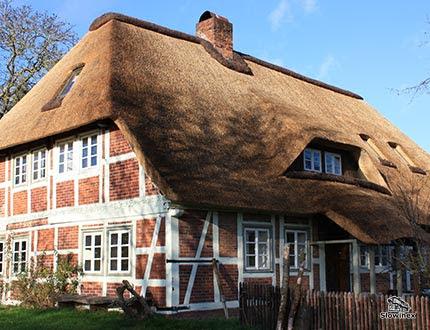 Duży dwupoziomowy dom z murem pruskie z białymi belkami i ceglanym wypełniem z dachem z trzciny