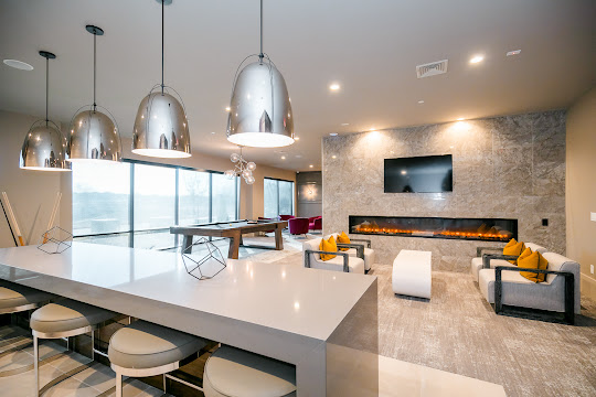 Community clubhouse seating area with mounted TV, fireplace, upscale finishes, modern hanging light fixtures, barstool area, and a billiards table