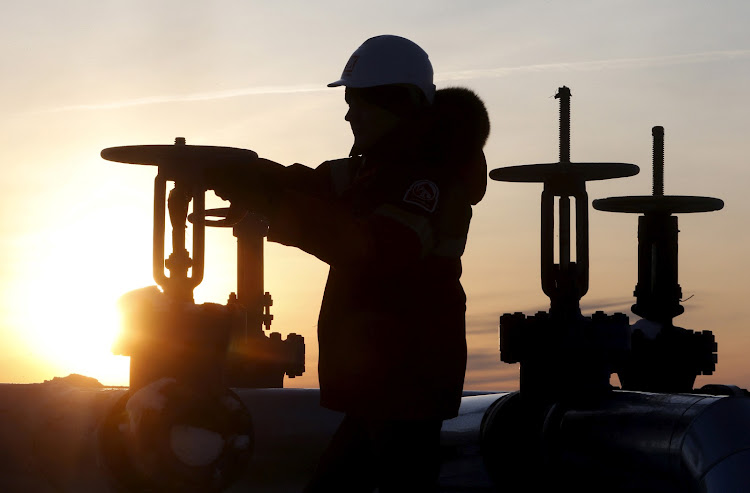 A worker checks the valve of an oil pipe at the Lukoil company owned Imilorskoye oil field outside the Siberian city of Kogalym, Russia. File Picture: REUTERS/SERGEI KARPUKHIN