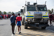 Pupils walk past a police Nyala on Thursday May 16 as protests over school overcrowding hit Kraaifontein, Cape Town, this week.
