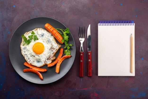 Top view of scrambled eggs with greens and sausages inside plate with notepad on dark surface