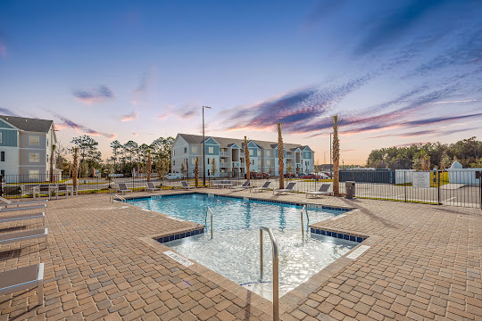 Pointe Grand Apartments sparking swimming pool at dusk