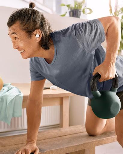 Un hombre mayor con una camiseta rosa y unos Pixel Buds A-Series color olivo hace ejercicio con unas pesas rusas.