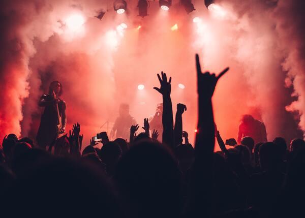 Foto de um show, onde você só consegue ver a silhueta das pessoas e um jogo de luzes vermelha
