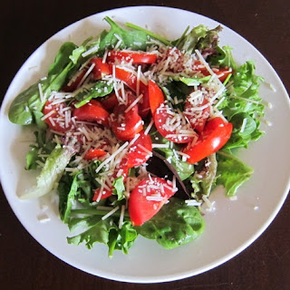 Lettuce And Tomato Green Salad With Shredded Parmesan Cheese.