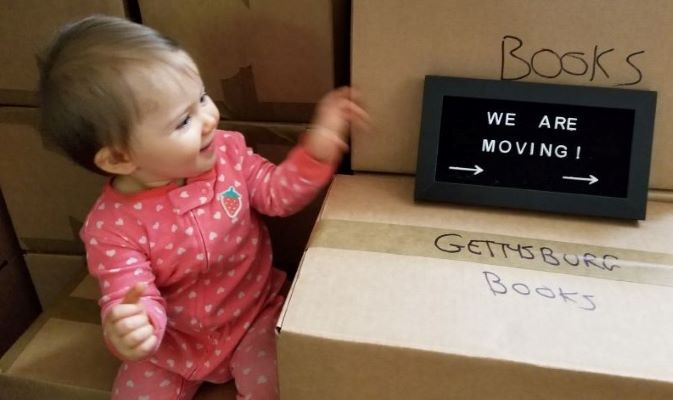 baby sitting on moving boxes during military move