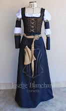 Photo: Vestido medieval em camurça preta com galões dourados e detalhes de camisa inferior, corset/colete feminino medieval em linho estampado, cinto com fivela e bolsinho em camurça. A partir de R$ 480,00.