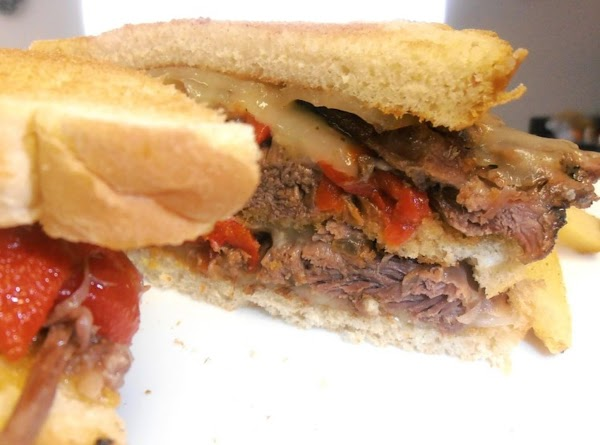 assemble sandwich:  toasted bread with melted cheese, beef peppers and cheese, toasted bread,...