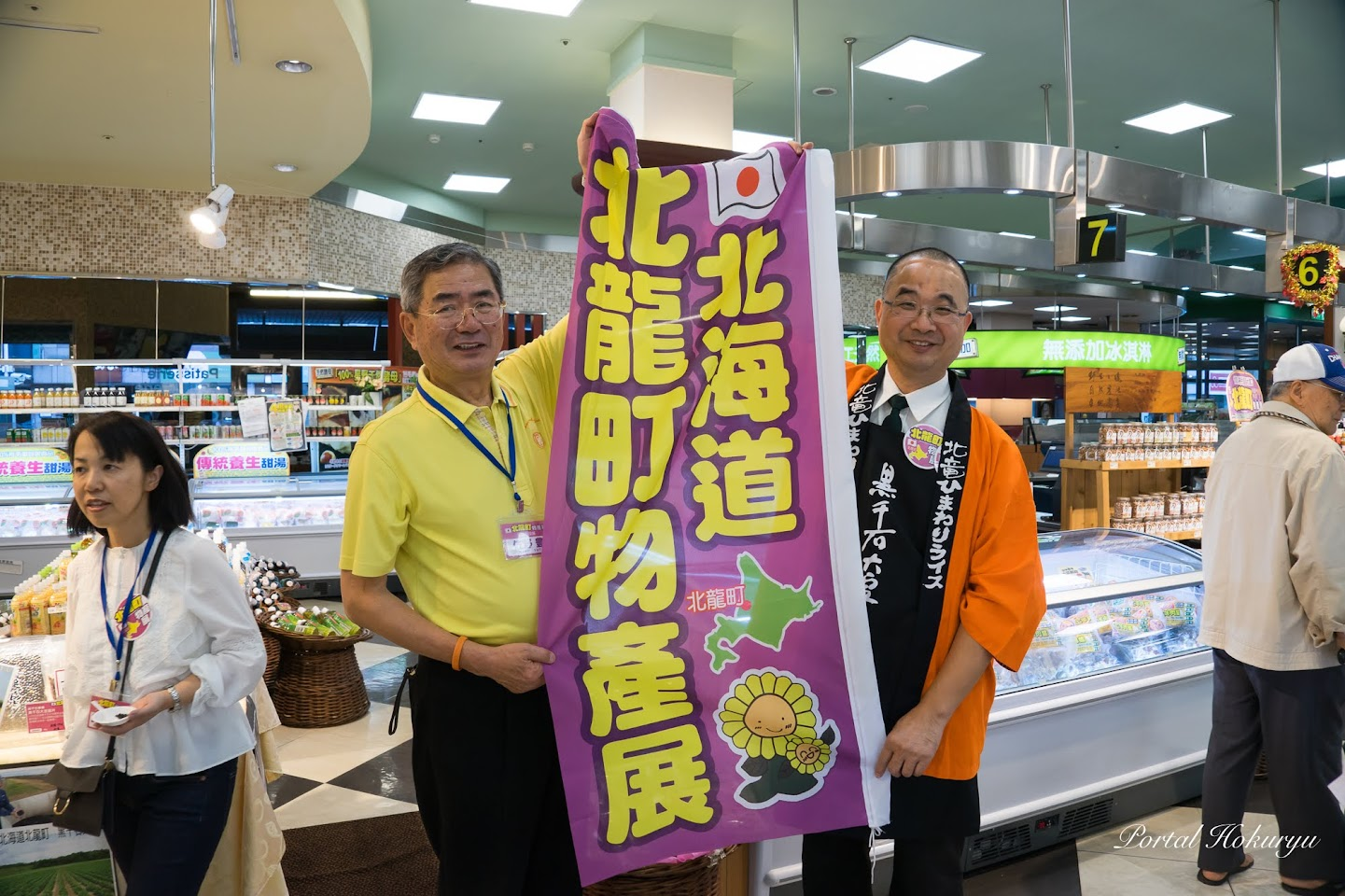 北竜町ひまわりライスの法被も裕毛屋公益店・邵栄泉 店長にプレゼント・佐野町長に、裕毛屋さんのノボリがプレゼントされました