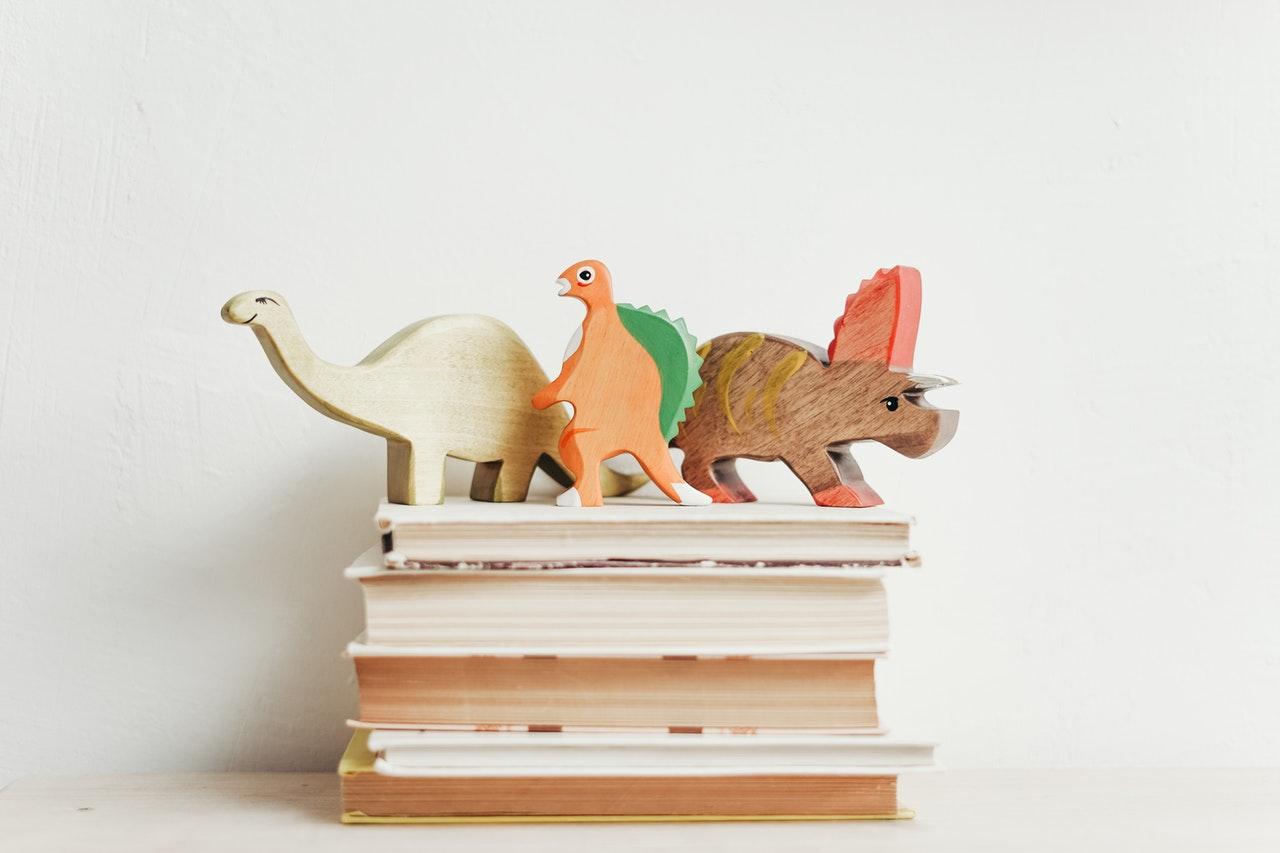Drewniane dinozaury położone na stosie książek na białym tle