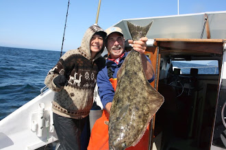 Photo: on the 3rd spot we all started catching our 2 limit p/p halibut. this was mine. have no clue how much it weighs but it was so damn hard reeling it in from 200 ft of water. very very tiring on the arms. Capt helps get them on the boat.