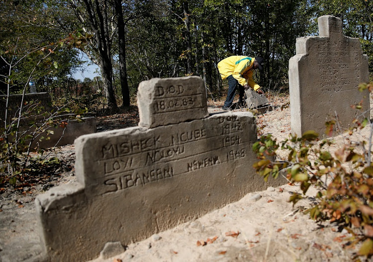Pastor John Moyo, 76, tends to the graves of people killed during a government crackdown on rebels loyal to Robert Mugabe's political rival Joshua Nkomo in the mid-1980s, site near Tsholotsho, Zimbabwe on June 23 2018. Picture taken June 23, 2018. Picture: REUTERS/PHILIMON BULAWAYO