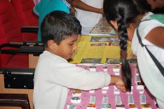 """Photo: A young Balvikas student explaining the """"Sai"""" Alphabets to a curious visitor"""