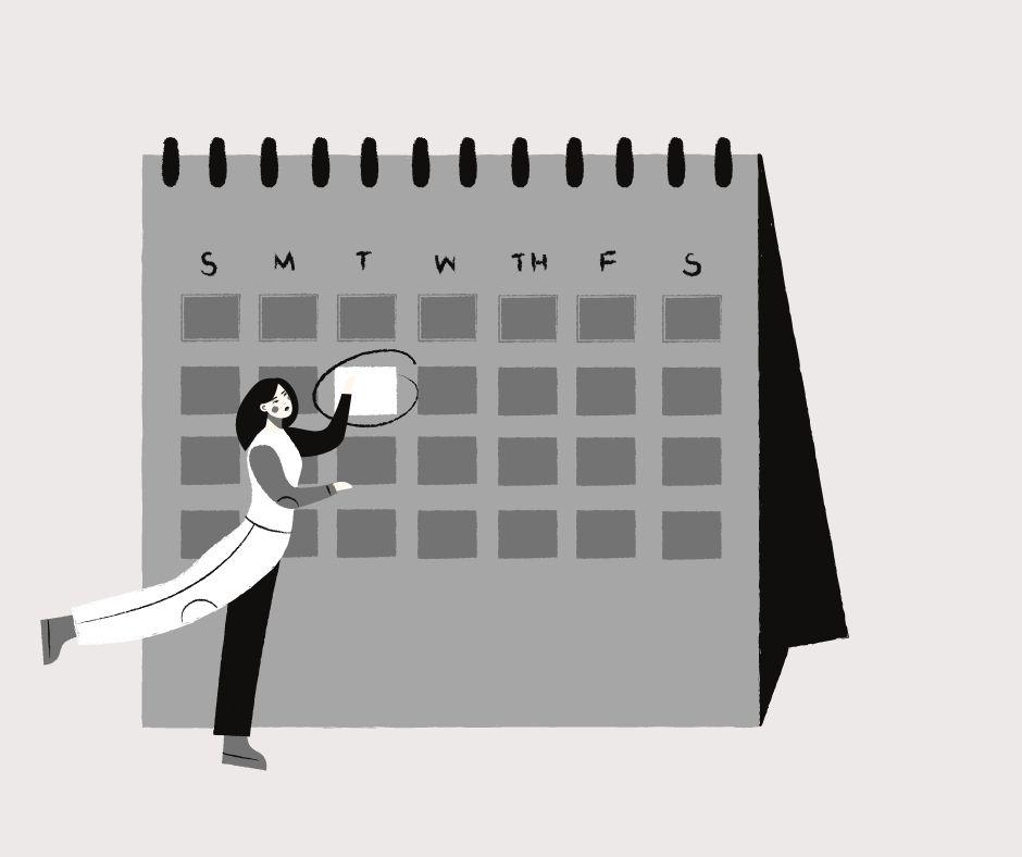 Woman marking a date on a calendar.