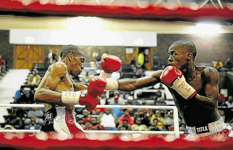 Thembelani Maphuma, left, and Lindile Tshemese exchange blows during their junior-bantamweight clash at the Orient.