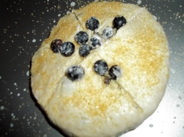 Scrape dough out onto a well floured surface and begin kneading in the blueberries...