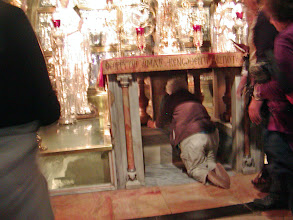 Photo: Pilgrims kneel under the altar to kiss the spot of Jesus' death.