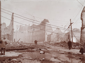 """Photo: Front at Bay looking East. """"The triangular facade of the ruined Phoenix Block can be seen in the centre of this photograph. Note the fallen telegraph and electrical wires, which caused difficulty and danger to the firefighters throughout the fire."""" - City of Toronto Archives"""