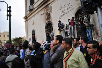 Photo: A crowd looks on as protesters, mainly youth, engage in rock-throwing clashes with the army.