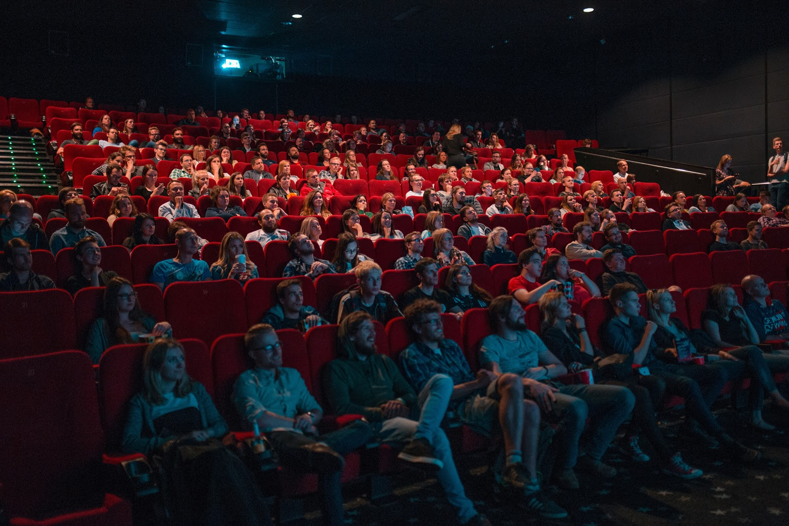 a crowd of people sitting in their seats at the movie theater