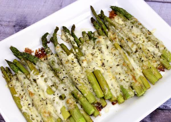 Cheesy Baked Asparagus Side Dish On A White Plate.