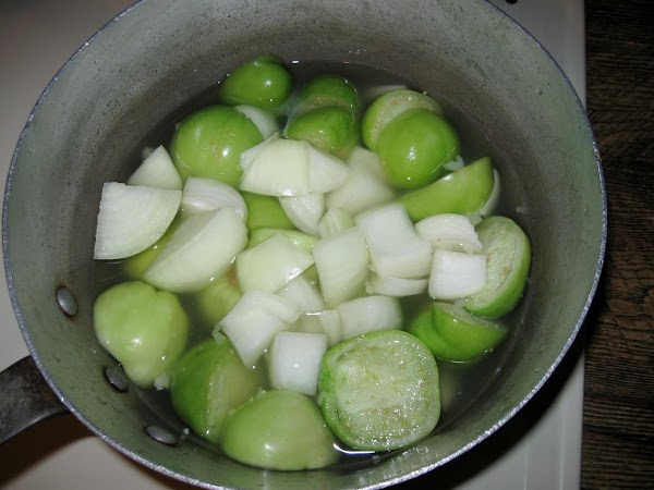 Peel the paper like husk from the tomatillo then wash them. Cut in half.