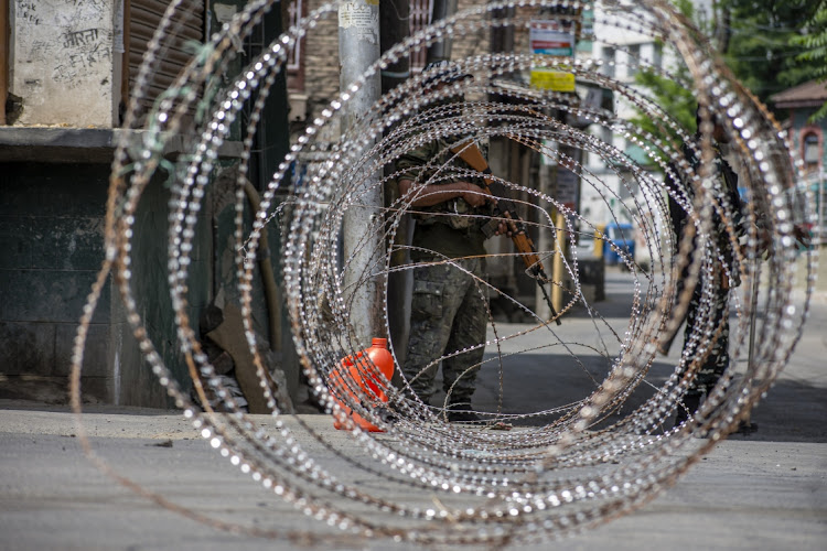 Indian paramilitary troopers stand alert next to their concertina razor wire in the old city during curfew in Srinagar, the summer capital of Indian administered Kashmir, India. Picture: Yawar Nazir/Getty Images
