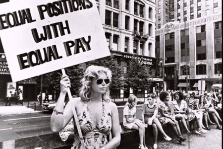 "This woman holding a sign calling for ""equal positions with equal pay"" shows the similarities among the waves of feminism, mainly activist work."