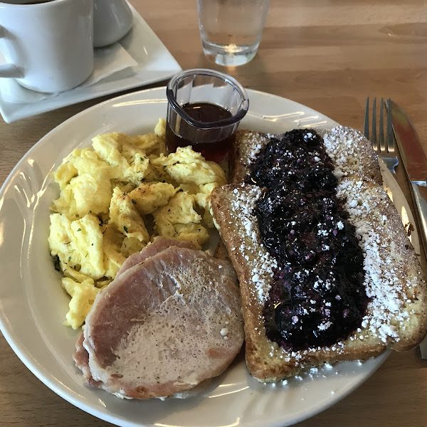 Gluten free french toast with cinnamon blueberry compote, bacon, and eggs.