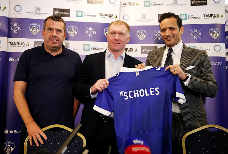 New Oldham Athletic manager Paul Scholes (centre) poses for photographs with owner Abdallah Lemsagam, right, and new assistant coach Mick Priest during a press conference on February 11, 2019. Picture: ACTION IMAGES via REUTERS/CARL RECINE