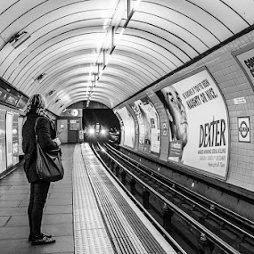 Waiting for the tube by Karen Shivas - Transportation Other ( tube, woman, white, pimlico, underground, posters, black, black and white, interior, building, monotone )