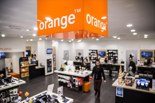 The Orange logo hangs inside a store in France. Picture: BLOOMBERG