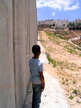 Photo: youth stands beside land, Ar Ram, near Al Quds (Jerusalem), encircled by Israeli Apartheid Wall in the occupied West Bank, encircling Palestinian villages, cutting Palestinians off from their land, separating families and neighbours, cutting off access to work, school, medical care.  Not about 'security'.
